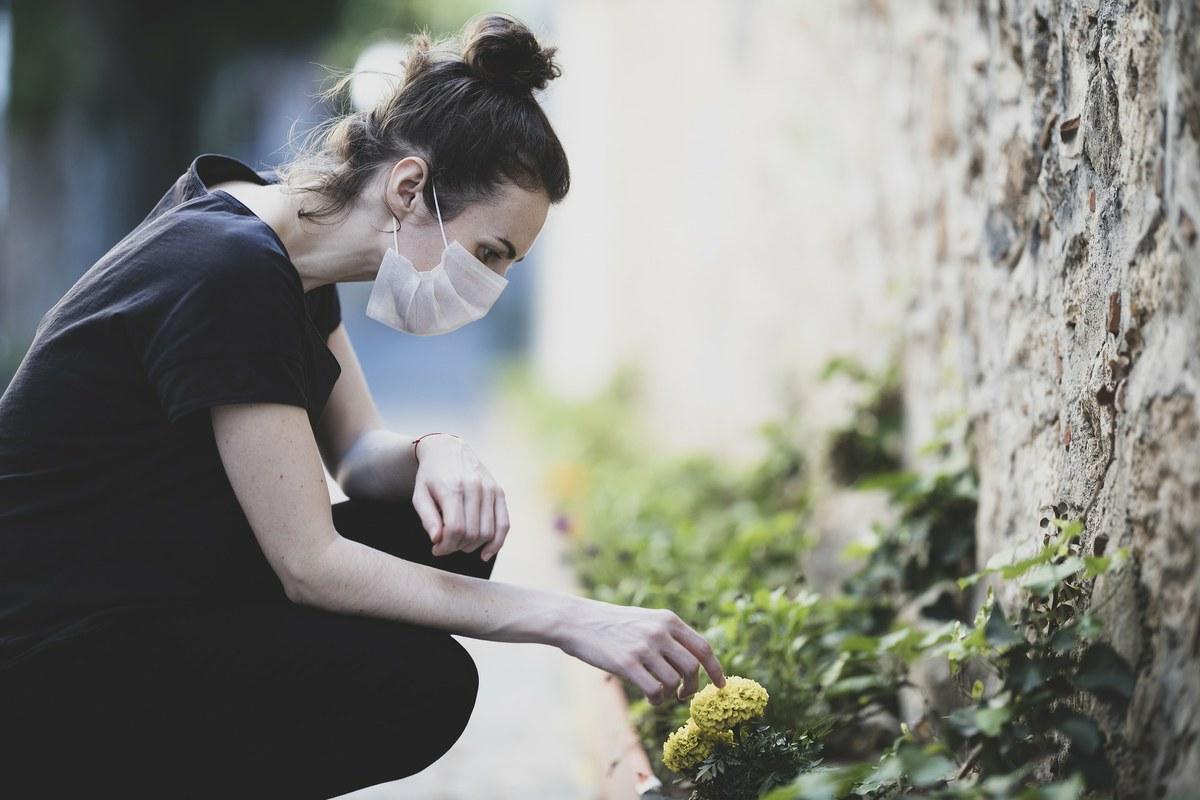 femme avec un masque touchant une fleur