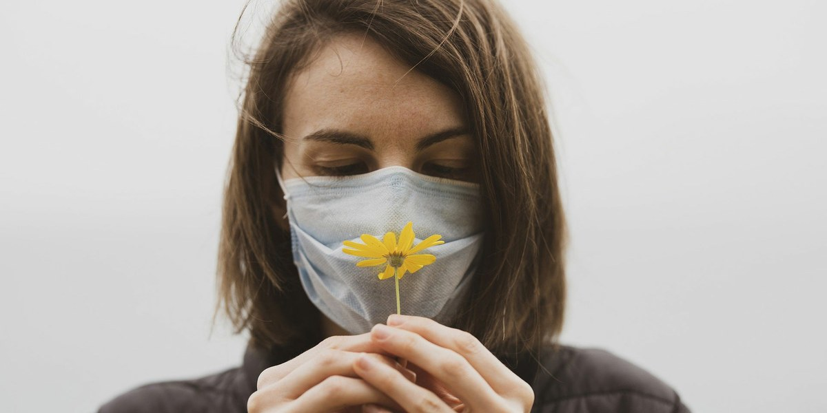 femme masquée tenant une fleur