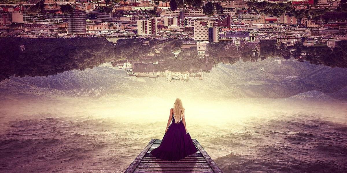 femme sur un pont regardant une ville à l'envers