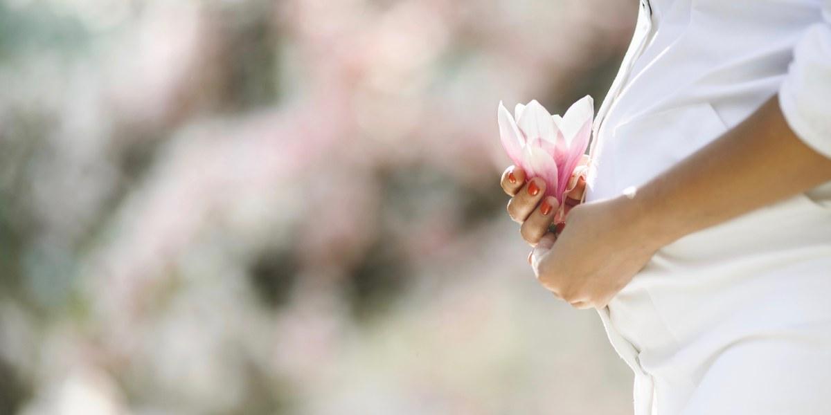 femme enceinte tenant une fleur rose